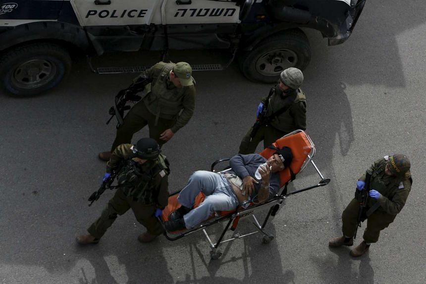 Israeli soldiers evacuate a wounded Palestinian man from the West Bank city of Hebron on Feb 13, 2016.