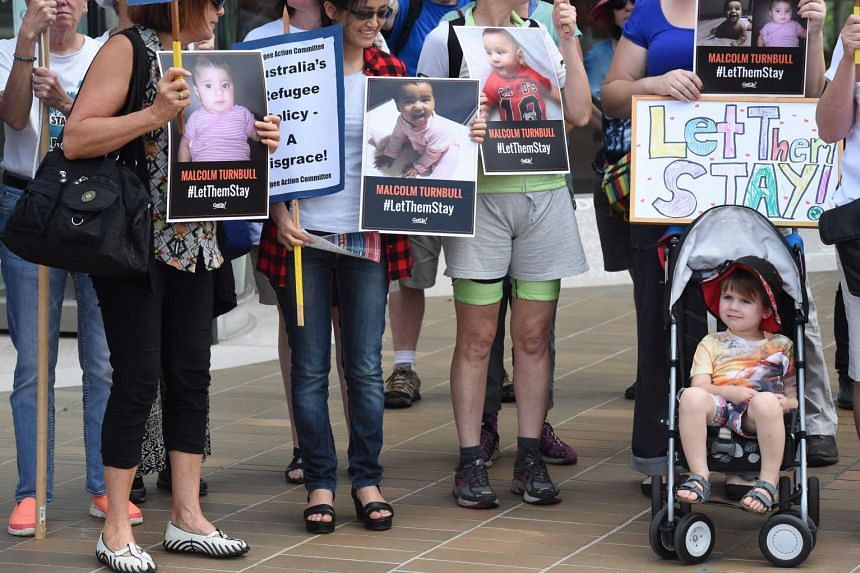 Activists with their toddlers holding signs and pictures of babies of asylum seekers who will be deported to Nauru, in Canberra, on Feb 3.