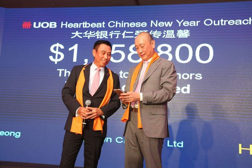UOB group head of commercial banking Eric Tham (left) looks on as UOB group deputy chairman and CEO Wee Ee Cheong keys in a $250,000 donation from the bank.