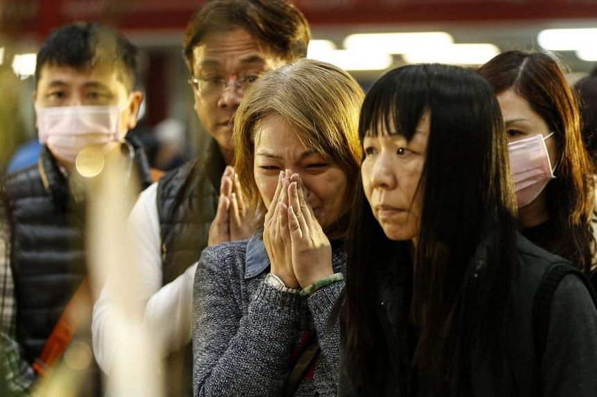 Grieving relatives attending a memorial service for quake victims in Tainan, Taiwan, on Feb 12, 2016. As the search operation ended on Feb 13, the focus now is to clear the rubble and disinfect the site, Tainan's Mayor William Lai said.