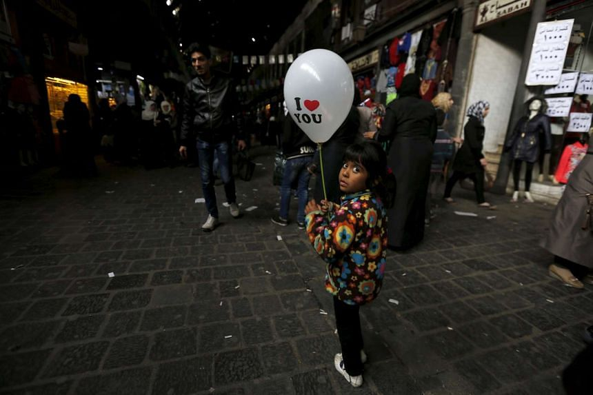 A girl carries a balloon ahead of Valentine's Day in al-Hamidiyah Souq, in Damascus, Syria on Feb 11, 2016.