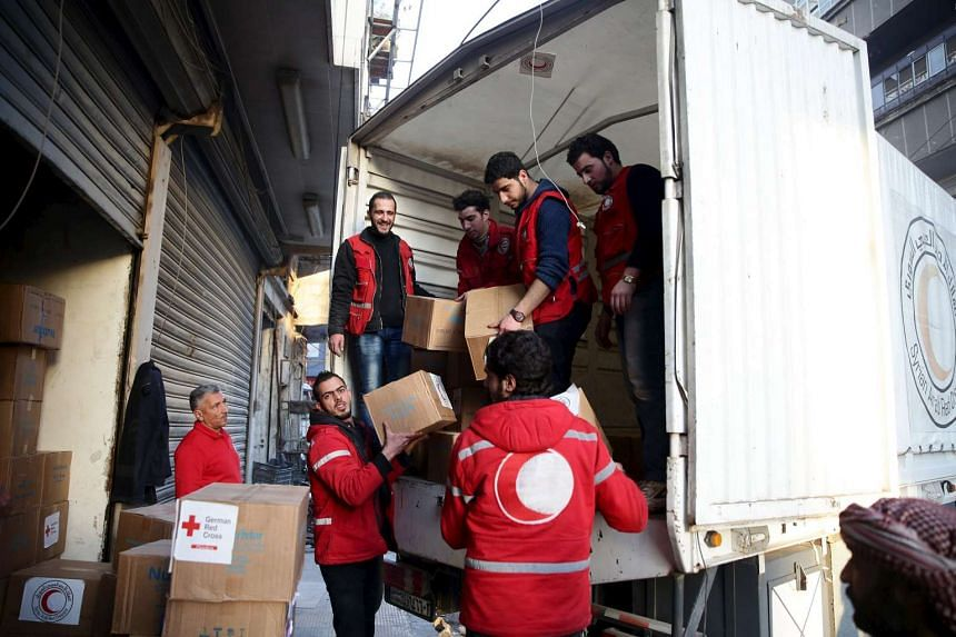 Red Crescent members unload aid boxes in the rebel held besieged city of Douma, a suburb of Damascus