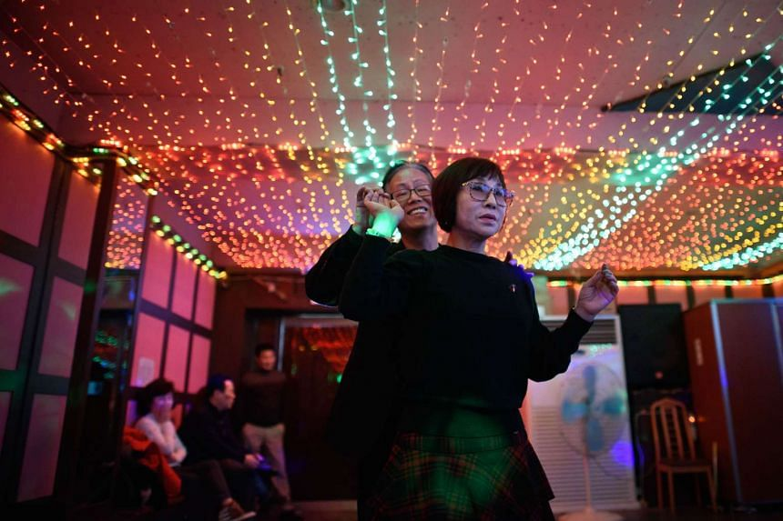 "A couple dancing at a Colatec in Seoul. South Korea's seniors enjoy themselves at clubs where 50-year-olds are turned away for being ""too young""."