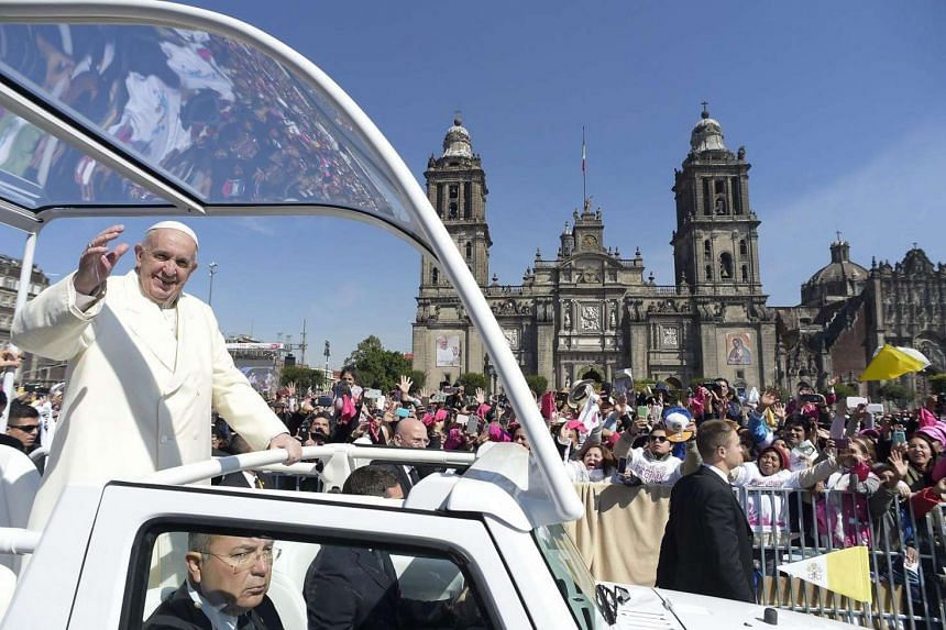 Pope Francis waves to the faithful from the popemobile as he heads to the cathedral for a meeting with Mexican bishops in Mexico City, Mexico, on Feb 13, 2016.