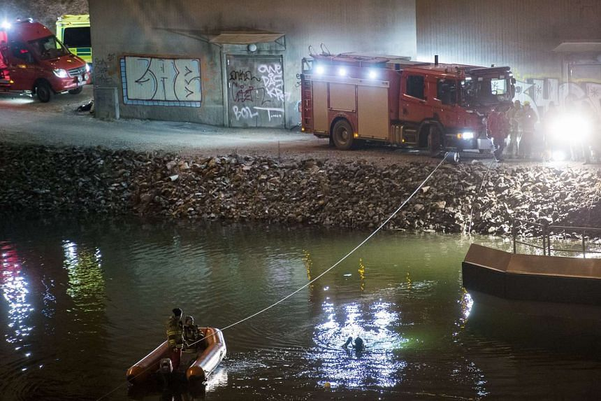 Divers and rescuers search for the victims of a deadly car crash, reported to be the members of British band Viola Beach and their manager, in the canal under the E4 highway bridge in Sodertalje, Sweden on Feb 13, 2016.