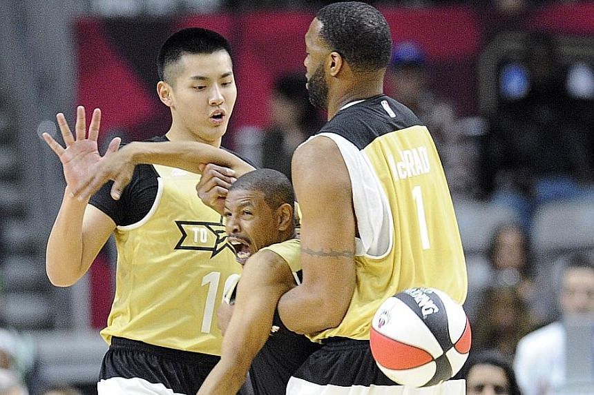 Canada player Kris Wu (10) looks on as team-mate Tracy McGrady (right) fouls USA player Muggsy Bogues (1.6m) during the All-Star celebrity game. The All-Star weekend is being held in Canada for the first time.