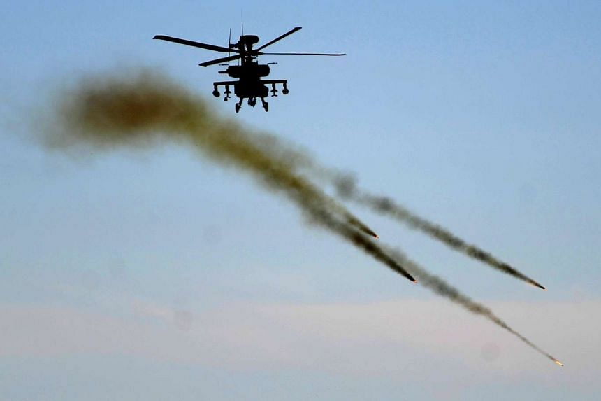 An Apache attack helicopter firing Hellfire missiles during an exercise at Fort Sill, Oklahoma, on Nov 18, 2009.