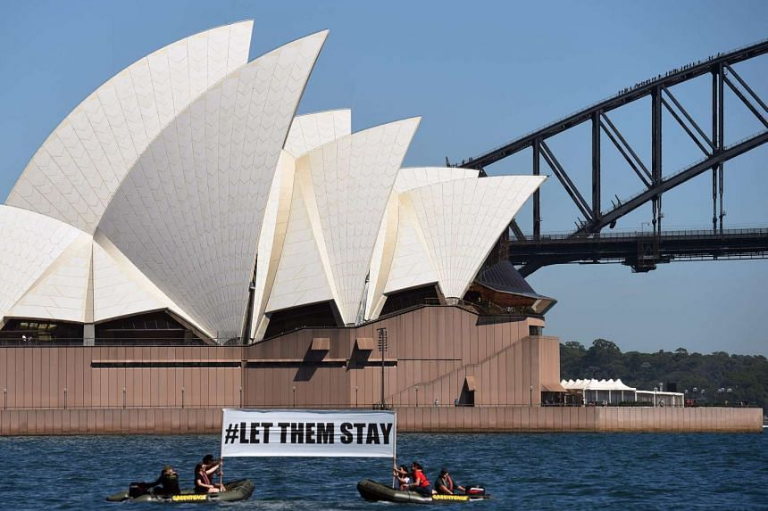 A group of demonstrators hold a protest sign on the harbour in Sydney, Australia, on Feb 14, 2016.