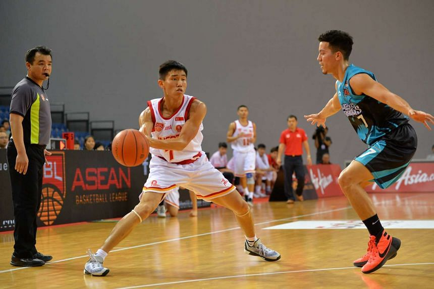 Singapore Slingers' Wu Qingde (left) looks to pass the ball against the Malaysia Dragons on Feb 14, 2016.