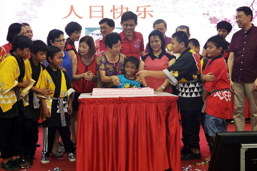 Mr Chan Chun Sing on stage with Madam Mak Kim Ho (centre, left) and Anif Suzaini (centre), who both have birthdays in February, as they cut a cake to celebrate Ren Ri, on Feb 14, 2016.
