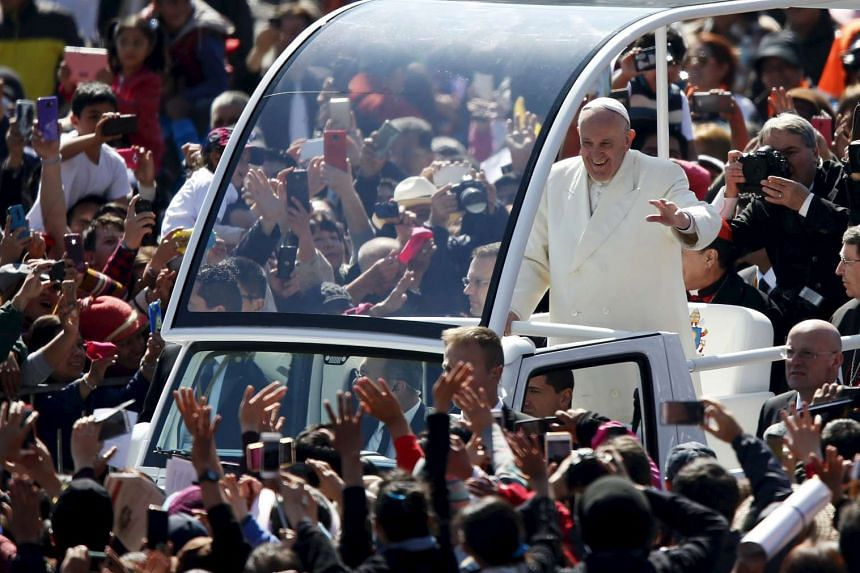 Pope Francis waves to the crowd from the popemobile in Zocalo Square in Mexico City, on Feb 13, 2016.