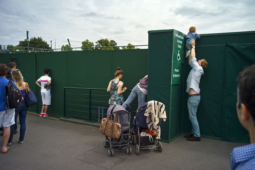 FIRST PRIZE, SPORTS CATEGORY, STORIES: Spectators with ground tickets finding creative ways of watching the play on Court 12 at the Wimbledon Championships. Spectators unable to secure tickets to any of the major show courts at the championships may