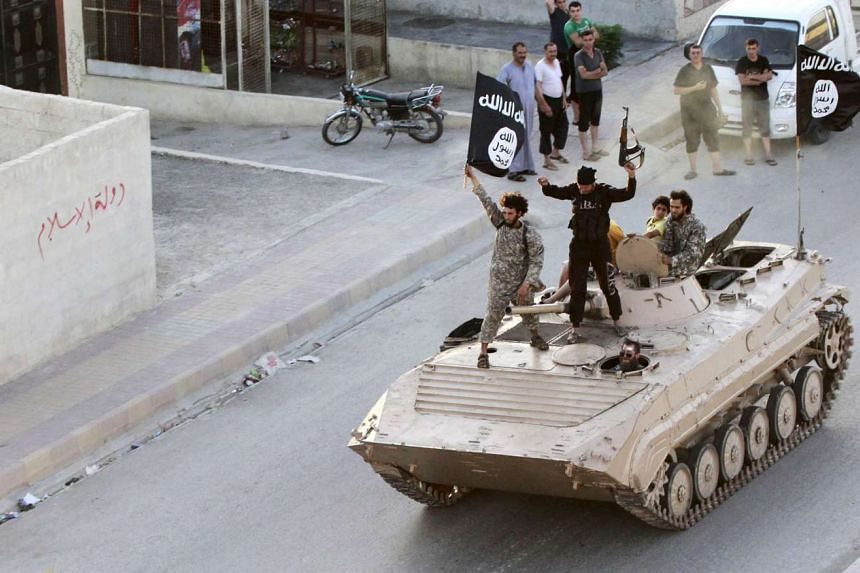 Militants waving ISIS flags ride an armoured vehicle through northern Raqqa on June 30, 2014.