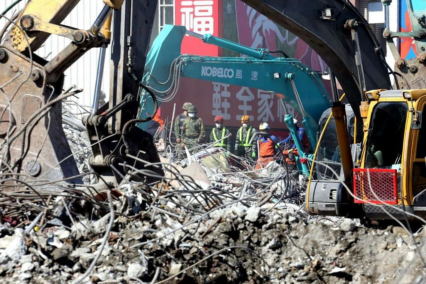 Heavy machines clearing up the remains of a collapsed building in Tainan City, on Feb 13, 2016.