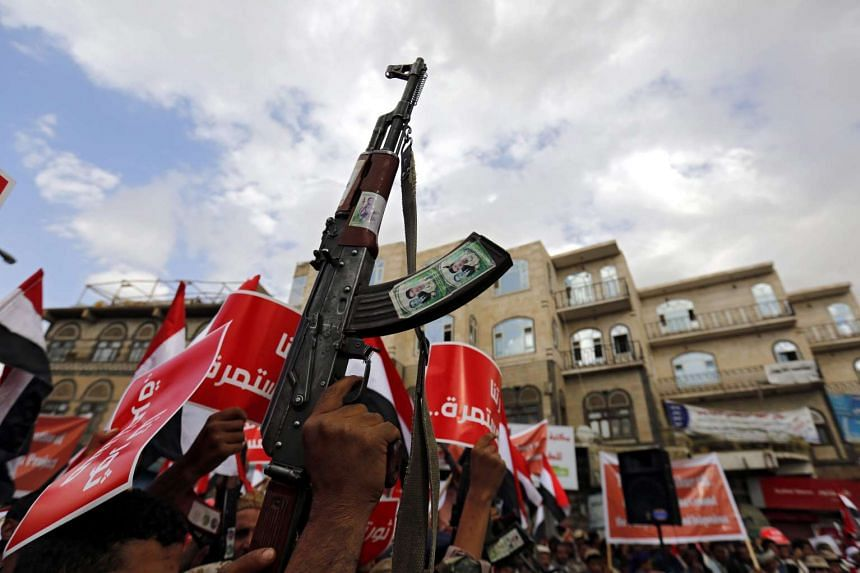 A Houthi supporter raises his weapon during a rally in Sana'a, Yemen, on Feb 11, 2016.