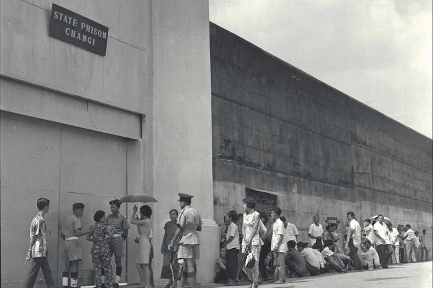 Friends and relatives of prisoners stand beneath the walls of Changi Prison in 1965.