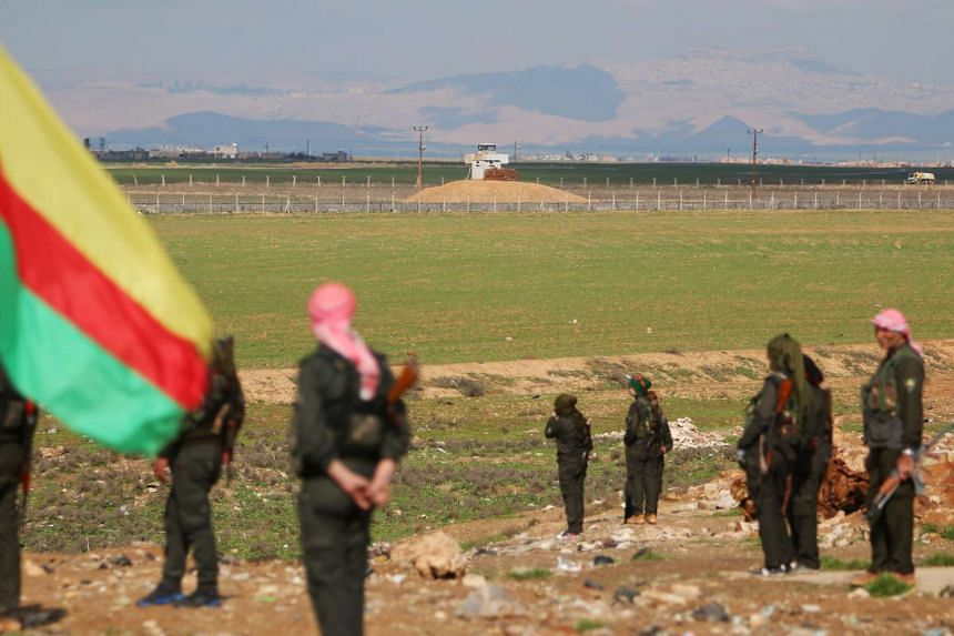 Kurdish members of the Self-Defense Forces stand near the Syrian-Turkish border in the Syrian city of al-Derbasiyah during a protest against the operations launched in Turkey by government security forces against the Kurds, on Feb 9, 2016.