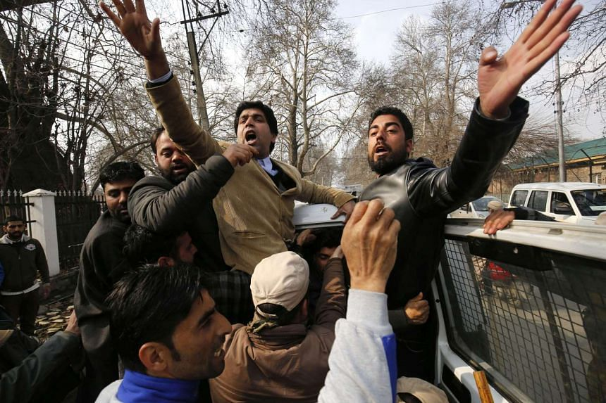 Supporters shout slogans from a police vehicle after they were detained during a protest in Kashmir on Feb 15, 2016.