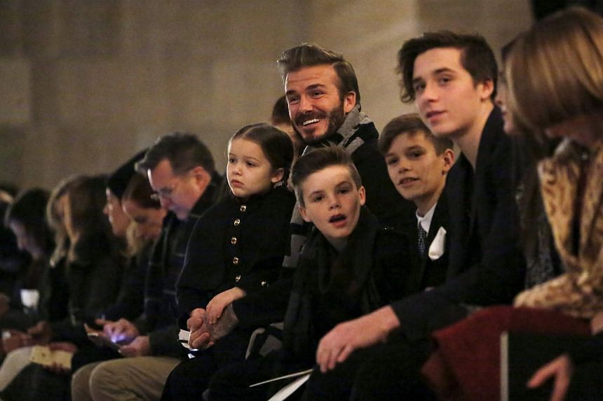 David Beckham sitting in the front row at the Victoria Beckham Fall/Winter 2016 collection presentation with his children Harper, Cruz, Romeo and Brooklyn on Feb 14, 2016.