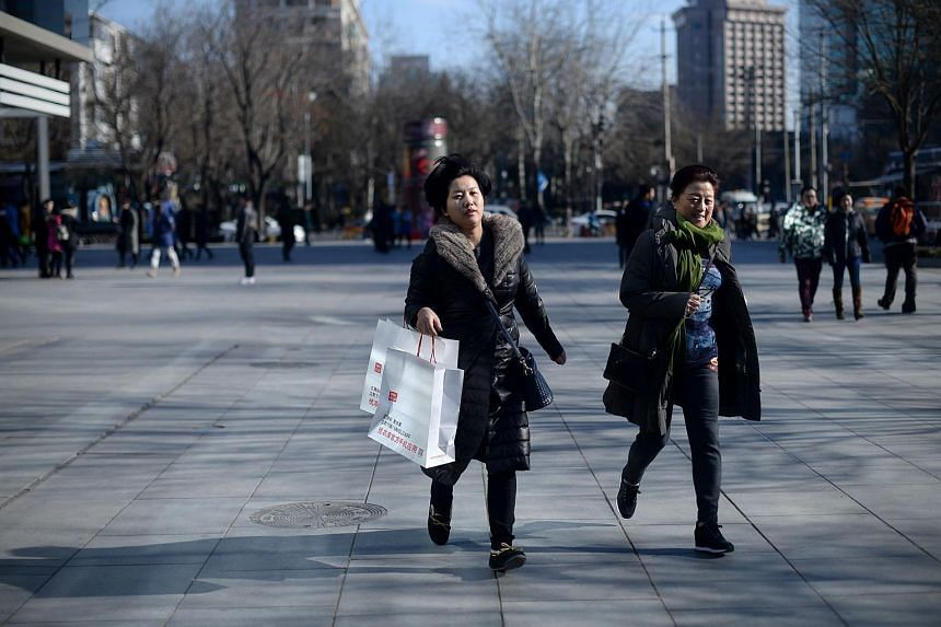 A woman runs with a bag outside a shop in Beijing, on Jan 13, 2016.