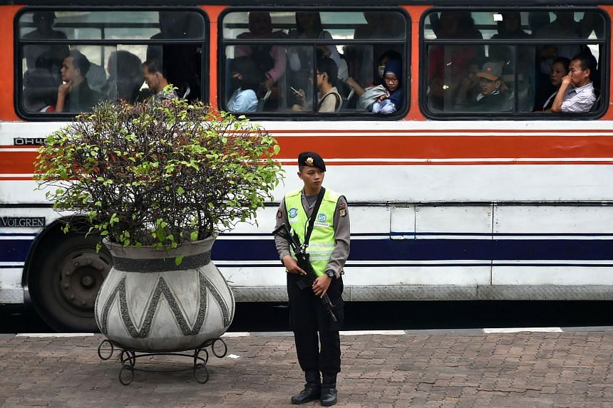 An armed policeman stands guard in Jakarta on Jan 22, 2016.