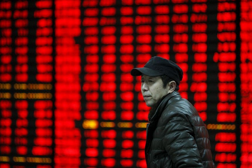 A man walking past an electronic board showing stock information at a brokerage house in Huaibei, Anhui province, on Jan 29, 2016.