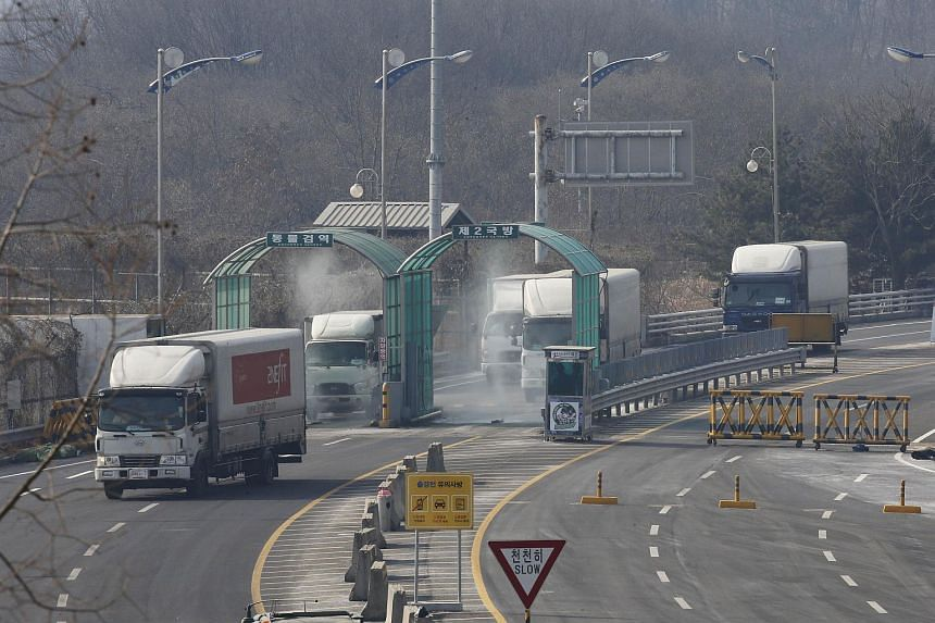 Vehicles leaving the Kaesong joint industrial zone pass through disinfectant spray before a checkpoint near the Demilitarized Zone separating North and South Korea, on Feb 11, 2016.