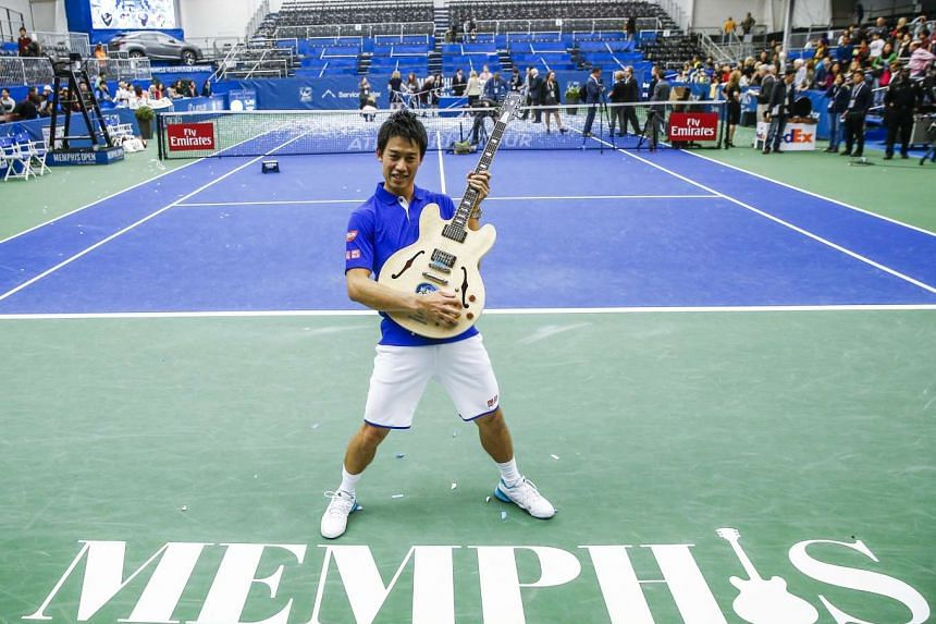 Japan's Kei Nishikori poses with the winner's trophy, a Gibson guiter, at the Memphis Open.
