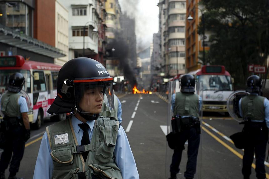 Riot police guarding a street where a fire was set by protesters at Mongkok district in Hong Kong, on Feb 9, 2016.
