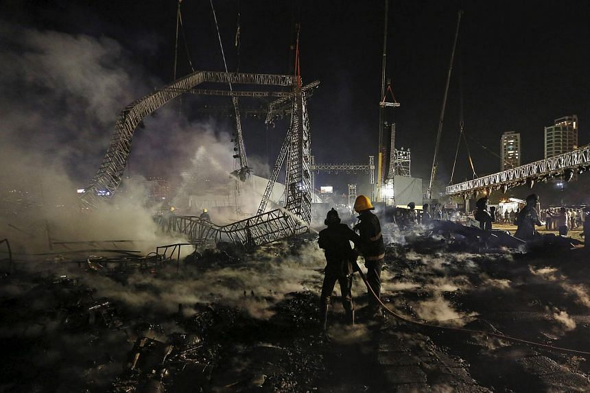 Firefighters try to extinguish a fire at the venue of a cultural event during 'Make in India' week in Mumbai, India, on Feb 14, 2016.