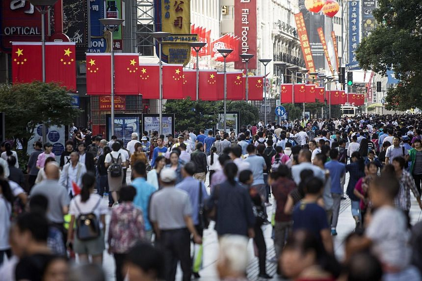 Pedestrians walk past Chinese national flags displayed along the Nanjing Road pedestrian street in Shanghai.