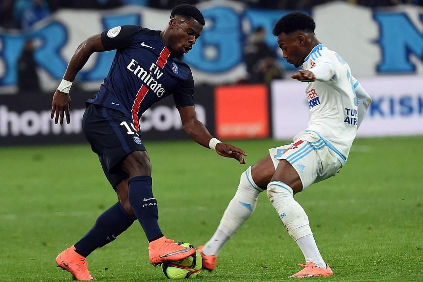 Marseille's Georges-Kevin Nkoudou vies with Paris Saint-Germain's Serge Aurier (left) during a French L1 football match.