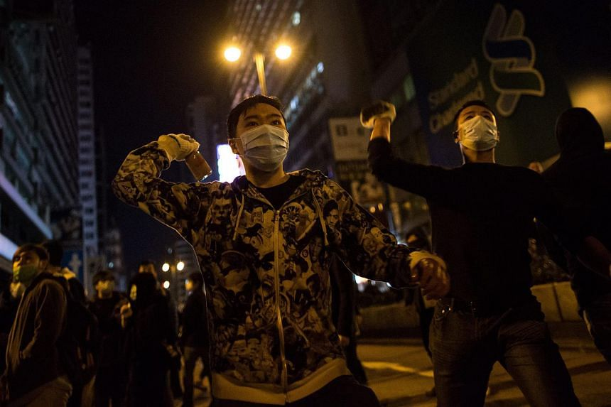 Protesters prepare to throw objects at police officers (unseen) during riots in Mongkok district in Hong Kong, China, on Feb 9, 2016.