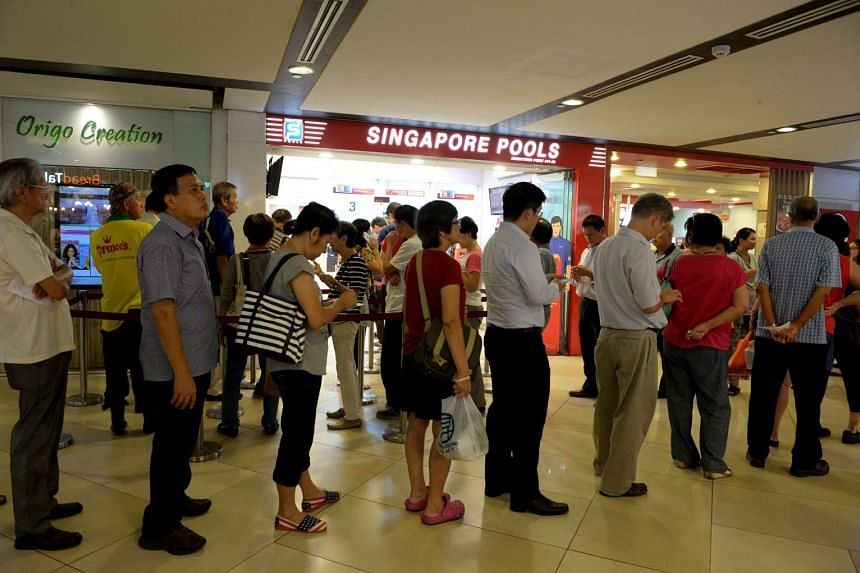 People queueing at a Singapore Pools outlet in Chinatown Point.