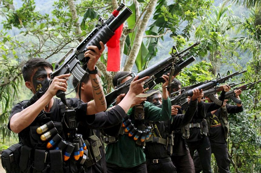 Armed members of the communist New People's Army aiming their weapons during a commemoration event, in Ifugao province on Dec 29, 2015.