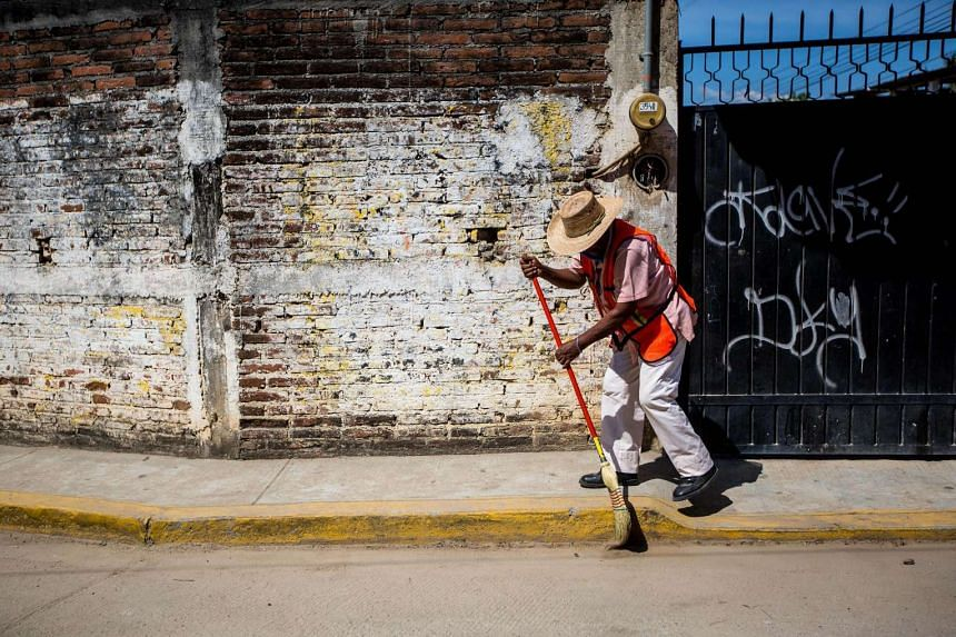 A municipality worker participates in a cleaning of the city to prevent mosquitos and the spread of Zika.