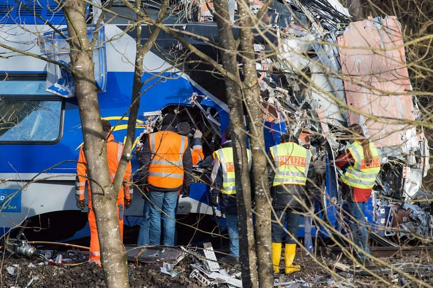 Emergency workers search wreckage at the train crash site for the third black box recorder on Feb 12, 2016.