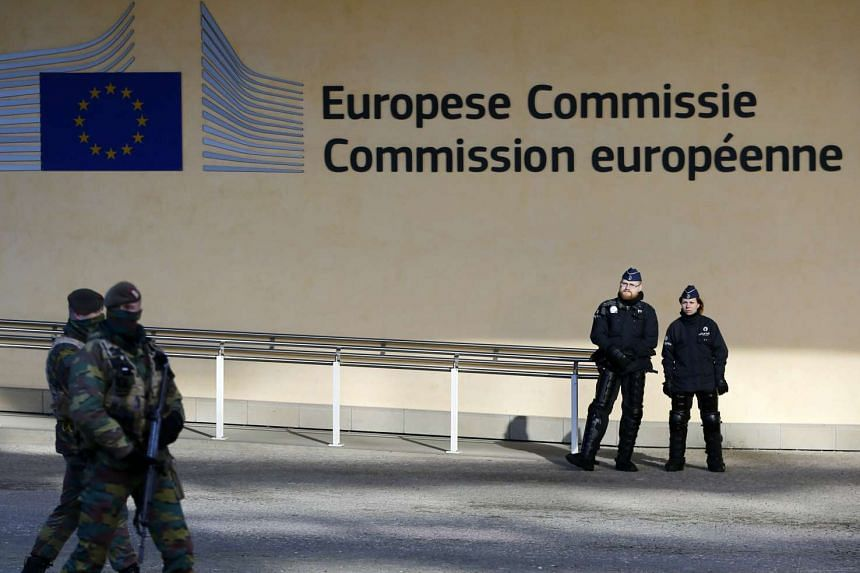 Belgian police officers stand guard as soldiers patrol along the European Commission headquarters in Brussels, Belgium on Feb 15, 2016.