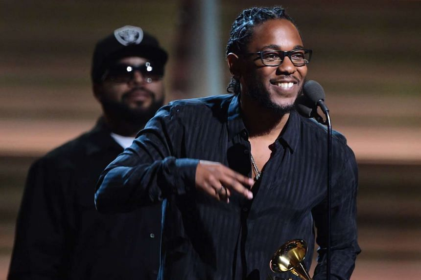 Recording artist Kendrick Lamar (right) recieves the award for the Best Rap Album, To Pimp A Butterfly.
