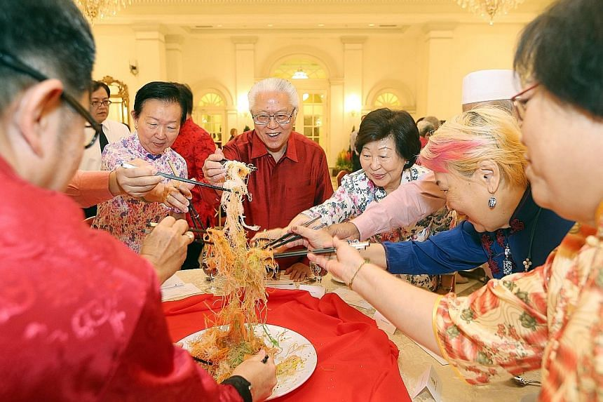 President Tan and Mrs Mary Tan tossing yusheng with seniors like Ms Chong (on President Tan's right), and Reach volunteers and staff.