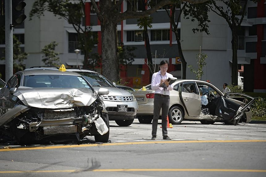 A police investigator taking notes at the scene of the crash involving a Volvo (left), a Hyundai (right) and a taxi yesterday.