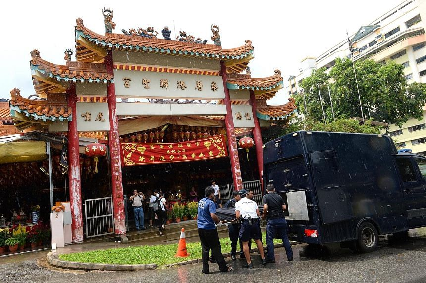 Police officers and undertakers removing the body of Mr Tan Poh Huat from the temple in Teck Whye Lane on Sunday. The victim's sister, Madam Tan Sui Kee, believes her brother had been carrying more than $10,000, as people had seen him exchanging note
