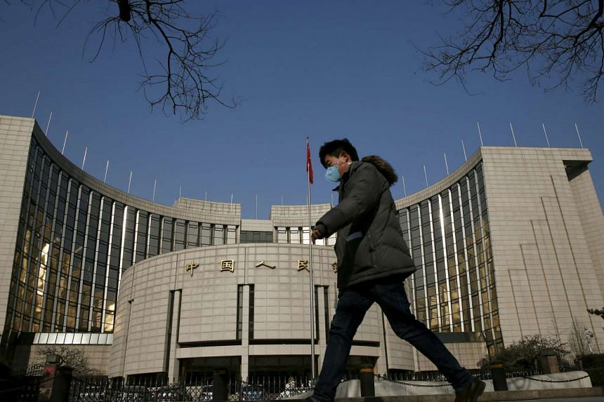 A man walks past the headquarters of the People's Bank of China in Beijing, China.