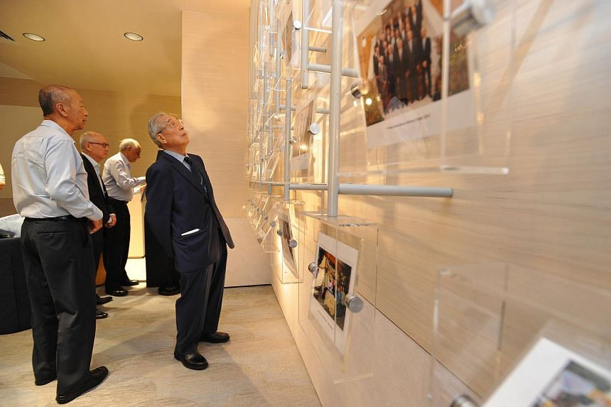 Mr Michael Wong, (right) MD from Dec 1970 to Feb 1981, viewing compilation of photographs at various events from MAS at The MAS Gallery on Feb 16, 2016.