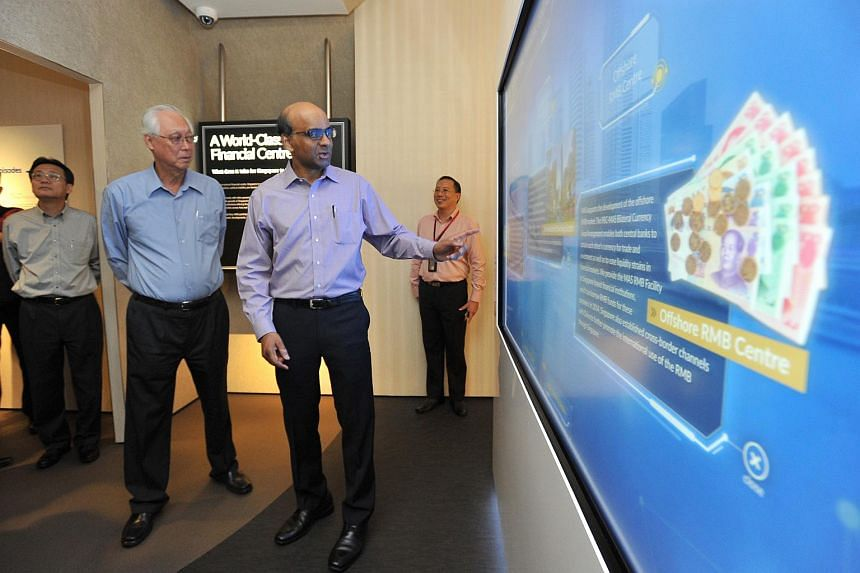 ESM Goh Chok Tong, and DPM Tharman, viewing an interactive display on Singapore as an international financial centre at The MAS Gallery on Feb 16, 2016.
