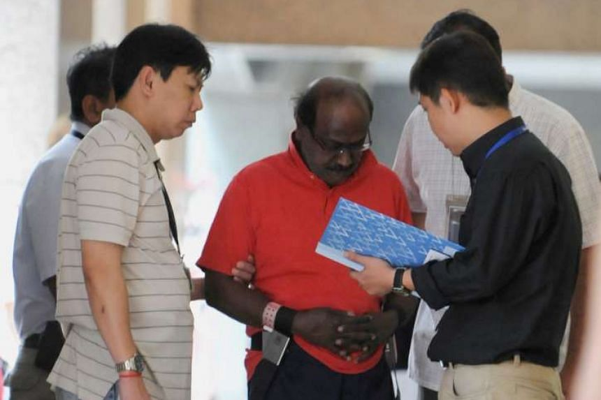 Govindasamy Nallaiah (in red) being escorted by policemen to the Afro Asia Building on Aug 17, 2011.