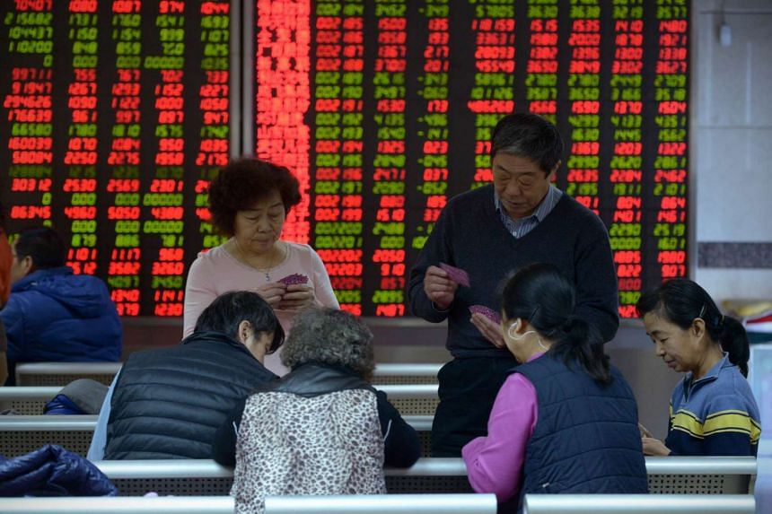 Investors play cards in front of screens showing stock market movements at a securities company in Beijing on Jan 8, 2016.