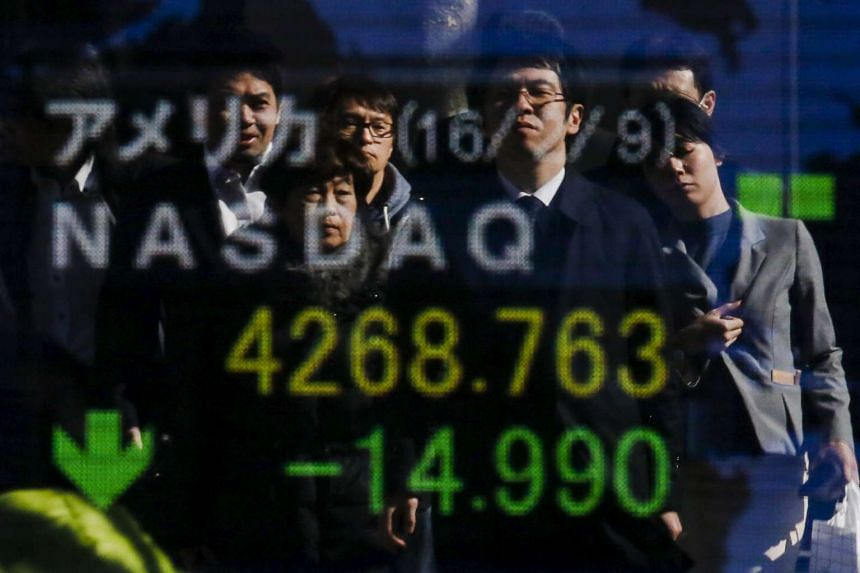 People are reflected in a display showing market indices outside a brokerage in Tokyo, Japan, Feb 10, 2016.