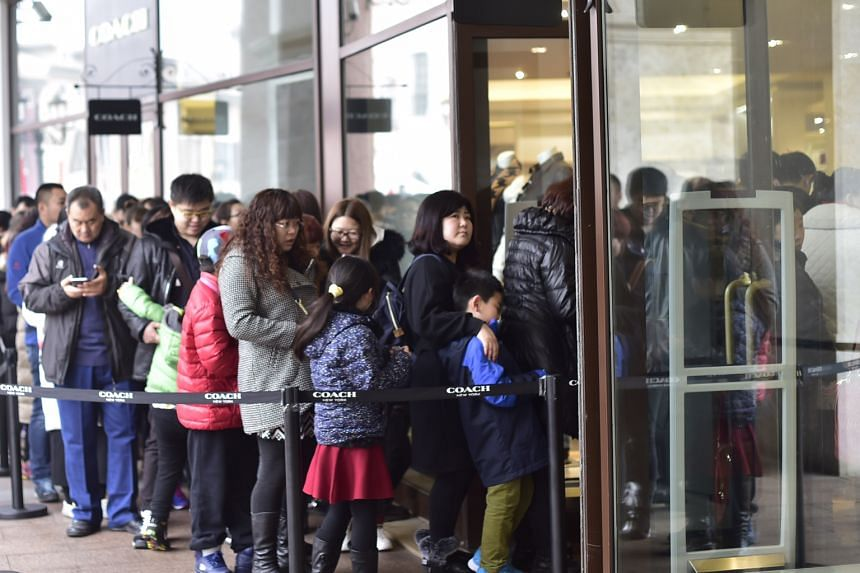 Meanwhile, others queued to enter a shop (above) in Florentia Village in Wuqing district, Tianjin, on the same day. The shopping village, which resembles a 16th century Italian town, features nearly 200 brand-name stores.