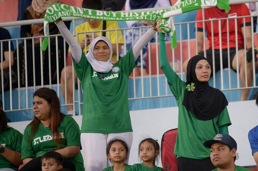 """Geylang supporters with """"You can't buy history"""" scarves. The Eagles dominated Singapore football from the late 1970s to the mid 1990s and were the champions in the S-League's first season in 1996."""